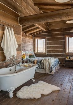 Cozy cabin great room, with a clawfoot bathtub, sheepskin rug, and Pendleton blanket draped on the bed.