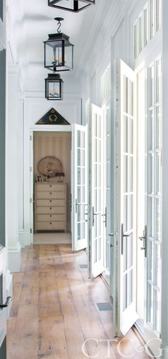 French doors in the main hallway are left unadorned to allow plenty of natural light. French Station Hanging Lanterns add light during the night or on cloudy days. Designed by Susan Z. Kessler and Eleish Van Breems.