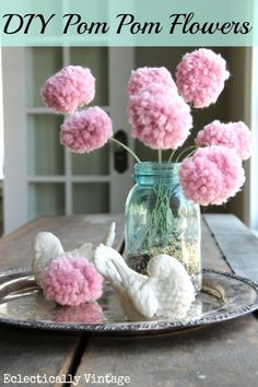 DIY Pom Pom Flowers - simple to make with just yarn and a fork!  You cannot love this idea...it's made with yarn and a fork!!  Now who doesn't have those two things laying around?!