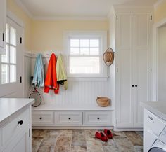 Bright and airy mudroom/laundry room with tiled flooring and lots of storage.