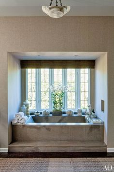A stone tub is tucked into a windowed alcove in music executive Jimmy Iovine's master bath | archdigest.com