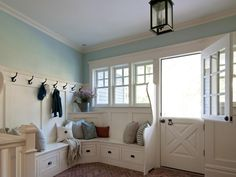 Although most mudrooms are linear, this one by Anthony James Construction makes great use of an odd corner near the entrances to the home's garage and backyard. A wraparound bench seat features ample storage underneath, while hooks stand ready for purses, jackets, backpacks and more. The 1970s Dutch door adds a nostalgic top note.