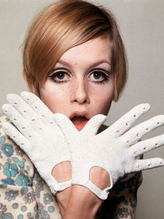 January 1966: A portrait of British model Twiggy wearing white gloves and a floral patterned blouse. (Photo by Popperfoto/Getty Images) Lesley Lawson nickname Twiggy is an English model, actress and singer. She became a prominent British teenage model of the Swinging 60's. Known for her thin build and androgynous look consisting of large eyes, long eyelashes, and short hair. Besides modelling she has had a successful career as a screen, stage and telly actress.