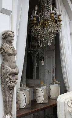 I love the way the French mix the ordinary (bottles) with the elegant/extraordinary (chandelier and statue)  via Trouvais