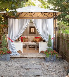 To make an outdoor room out of an empty space, simply put up a freestanding canopy. The canopy provides shade and minimal structure for an outdoor room. An area rug helps to further outline the space and a matching couch and chair set leave the room feeling cohesive. Attach curtains to the canopy for additional shade and privacy. Planters on either side of the canopy's entrance and stepping-stones leading to the structure help the space feel a bit more grand and permanent./