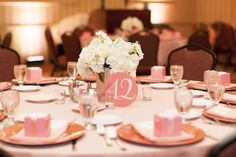 Simple white flower centerpiece with circle table number. But in mint