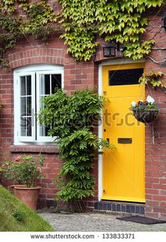 Yellow front door entrance and old style window of a red brick house or a cottage with hanging flower basket and green ivy.