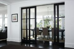 I love this look black and white the dining room open yet shut with the use of sliding glass doors A-Dining Room