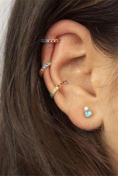 Our Rainbow Zirconia Ear Cuff hugs the ear with delicate and cheerful rainbow gem detailing for added cool, without a new piercing. These babies like to be with friends so be sure to check out our other rainbow zircon earrings! - Composition: 14K gold plated over .925 sterling silver or solid .925 sterling silver, multi-colored CZ stones - Measurements: inner diameter 10mm, stones; 1mm Ear Jewelry, Body Jewelry, Cuff Earrings, Diamond Earrings, Raw Crystal Jewelry, Silver Ear Cuff, Affordable Jewelry, Or Rose, Ear Piercings