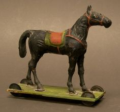 "Extra Large Early Tin Platform Horse on wooden base with original tin wheels. Note the large size of this 19th century tin toy. It measures 11"" x 4"" x 10"" tall."