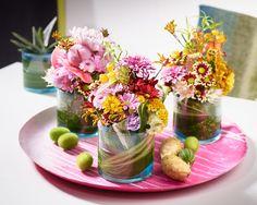 Floral Camouflage. Kontrastreich, bunt und effektvoll ist diese kleine blumige Chrysanthemen-Dekoration. Die kleinen Muntermacher im Glas wirken für sich oder in der Gruppe.