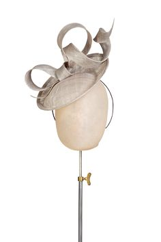 Wonderfully fun hand shaped bow sits atop a disk.  Worn at an angle to  create a dramatic effect.  An excellent and versatile addition to any  wardrobe.  Secured using a bound wire headband available in black, brunette, blonde or  grey to match your hair colour.  Measurements: disk 28cm.  M