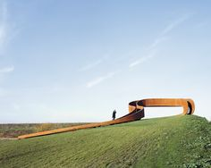 Built by NEXT Architects in Barendrecht, The Netherlands with date 2014. Images by Sander Meisner. A rusty steel ring is gently draped upon a grass hill in Carnisselande, a Rotterdam suburb. It's a giant circular sta...