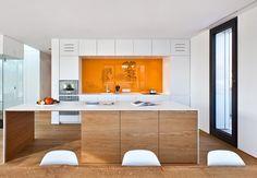moderne Küche weiß Holz Kochinsel orange Glas Spritzschutz