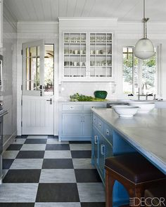 """The spacious kitchen is period correct, with a Dutch door, Marmoleum patterned to resemble the marble checkerboard of a dance floor, and a paint color that morphs from blue to gray to pale green. """"It's not a white kitchen,"""" Stuart declares. """"If I see one more of those, I will hang myself.""""  The kitchen counters are quartzite, the cabinetry is custom made, and the flooring is Marmoleum  Madeline Stuart Beverly Hills Home - Arts And Crafts Cottage - ELLE DECOR"""