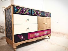 Is a multicolored unique piece of art that is intensely, yet elegantly covered with intricately painted patterns. The crystal glass top, see through upholstered drawers and unique knobs make this piece a gyld to your home.