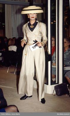 Modevisning. Modell i beige byxdress, hatt och smycken. Från Chanel.