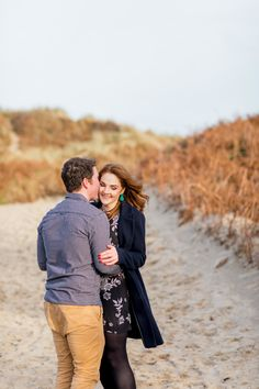 a couple posing for an engagement shoot wearing a black checkered shirt with khaki chinos and a knee length black dress with white flowers and green earings Couple Posing, Couple Photos, Ireland Beach, Catch A Flight, I Respect You, Donegal, Engagement Shoots, White Flowers, Red Hair