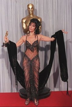 "Cher, never afraid to push the envelope of good taste, shows off her Oscar for best actress and her Bob Mackie black sequined see-through gown after winning the award for her role in ""Moonstruck"" at the 1988 Academy Awards.  Lennox McLendon/ AP"