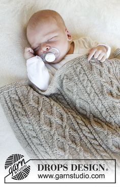 Knitted blanket with cables for baby. Piece is knitted in DROPS BabyMerino.