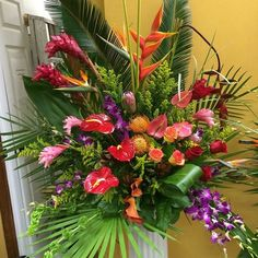 Alter arrangement of torch ginger, anthurium, dendrobium orchids, High Magic roses, red roses, pin cushion protea, Pink Ice protea, birds of paradise, calla lily, Bihai (yellow and orange)heliconia and hanging Rostrata heliconia, Bells of Ireland, solidago, Ti leaves, Sago palm, lemon leaf, variegated monkey grass, palm fan and Teepee. DorisTheFloristt.com