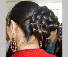 A massive bun made on long and dark hair, decorated with a metal stick for a breezy look