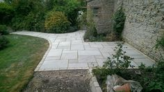 A simple grey sandstone patio and path enhance this cottage garden. Designed and built by SilverBirch Gardens Ltd