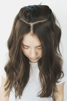 """Step 1: Part Your 'DoMimic the parting that Ess has created here using your comb. The goal is to create a soft """"Y"""" shape. The shorter your forehead, the longer the bottom of the """"Y"""" should be. Smaller foreheads can stick to two inches or more; longer foreheads can do one inch or less.Section the hair behind it to keep it out of your way. #refinery29 http://www.refinery29.com/2016/10/127226/how-to-style-fake-bangs-hair-trend-tutorial#slide-3"""