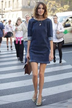 Alexa Chung in a cute denim shift-style mini dress. Bateau neckline, cuffed elbow length sleeves. Brown handbag, looks like some sort of skin. Delicate pendant and neutral pumps. Lovely. Very minimal. Style Planet