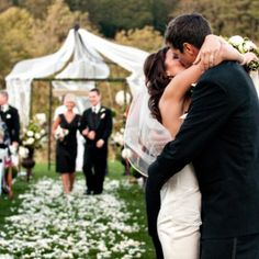 A stolen kiss! Romantic shot with gauzy cloth blowing in wind and petaled aisle. (By Soul Mates Photo)