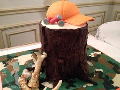 """The Hunt is Over Groom's Cake - Hunting-themed groom's cake for a wedding on the opening day of deer season. Message carved in the trunk says, """"The Hunt is Over — E + R."""" Six layers of pumpkin spice cake covered in buttercream and modeling chocolate """"bark."""" Hat is also pumpkin cake covered in fondant. Antlers are hand-painted and carved white chocolate. Rifle shells and camouflage base are made of fondant."""