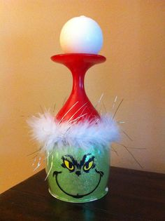 Grinch Candle Holders: inspired by other pinners, I made 10 of these using Dollar Tree wine glass, green glitter on the inside (using Glitter-It), red Krylon spray paint on outside, Cricut vinyl face, white feather boa (attached with hot glue), and a round, white candle.