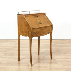 This antique secretary desk is featured in a solid wood with a rustic tiger oak finish and shiny brass accents. This slant front desk has delicate legs, 1 drawer and a drop front desk with blue painted interior storage. Eye catching desk perfect for a small workstation!  #americantraditional #desks #secretarydesk #sandiegovintage #vintagefurniture