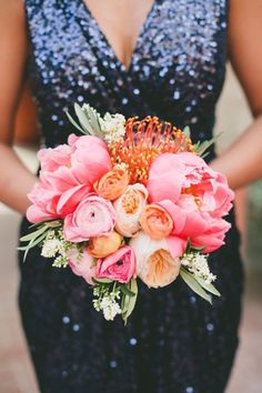 Bright bouquet with Coral Charm peonies, Juliet garden roses, ranunculi, and a pincushion protea | Photo by Onelove Photography