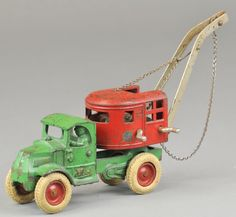"c. 1932, cast iron, green enclosed cab with cast driver at window, side cranks wind chain on windless rear cab able to swivel, rubber tires, red hubs, decal on body. 11 1/2"" l."