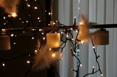 Fairy lights with feathers hanging from a lamp! #fairylights