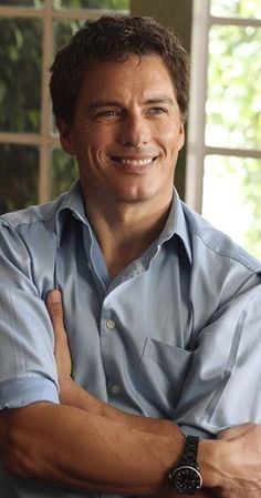 """John Barrowman, Actor: Torchwood. Born in Glasgow, Scotland, and raised in Joliet, Illinois. He returned to the UK, for a 6 month Shakespeare semester with the United States International University of San Diego, but left to star in the musical production of """"Anything Goes,"""" with Elaine Page. He went on to star in """"Miss Saigon,"""" """"Matador,"""" """"Rope,"""" and """"Hair"""" at London's West End. Barrowman has homes in London and Cardiff, Wales."""