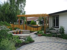 Defining the circular patio area with a low wall, surrounded by ground-level flower beds