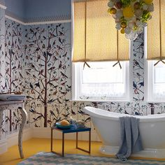 Bathroom with bird wallpaper and white freestanding bath