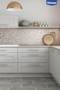 This on trend blush copper and metallic mosaic tile shot has a refined sophisticated look. The simple light grey shaker kitchen doors are teamed with slate grey floor tiles and a solid quarts worktop. Shaker Kitchen Doors, Grey Shaker Kitchen, Grey Kitchen Cabinets, Shaker Cabinets, Kitchen With Grey Floor, Pink And Grey Kitchen, Grey Kitchen Tiles, Grey Cupboards, Grey Shelves