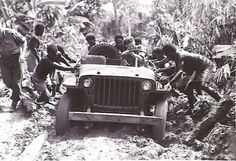 Soraken area, Bougainville, 1945-06-16. Captain W. Kennedy, officer commanding 11 infantry brigade signals (2), lieutenant W R Thompson, guard platoon, 11 infantry brigade (1) and natives getting a Jeep out of a bog on the east/west track. The linesman had left the vehicle and was laying lines ahead.