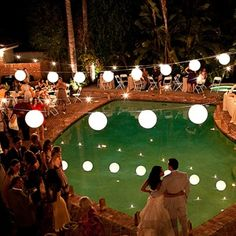 Renita and Alex's friend and planner Katrina Teeple turned their friend's backyard into an elegant reception space decorated with string lights and paper lanterns with floating candles in the pool for a romantic touch.