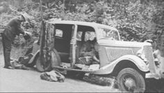 Lawmen unload Clyde's traveling aresenal. The bodies of Bonnie & Clyde, dead in the car,will remain inside until the vehicle is towed.
