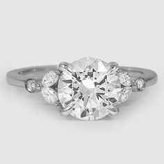 This feminine, nature-inspired ring features four dazzling marquise shaped diamonds elegantly accenting the center diamond.