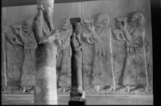 Two Neo-Assyrian relief slabs representing tribute-bearers from Urartu, from Dur Sharrukin (Khorsabad); 721-705 B.C. In the foreground, two ritual statues of the god Ea, found at the entrance of the Temple of Sin, from Dur Sharrukin (Khorsabad) (IM. 25963 or IM. 11949).