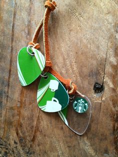 Three guitar picks made from a Starbucks gift card dangle in a sort of tassel from a length of burnt orange leather strap. Silver plated toggle