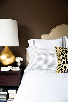 Brown bedroom with leopard print pillow, neutral headboard, gold lamp, and white bedding