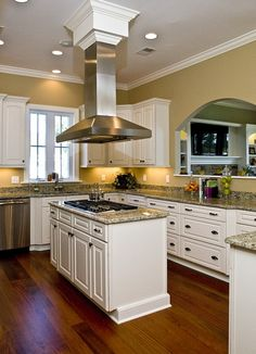 A stylish range hood hangs over an island with a built in for Kitchens with islands in the middle