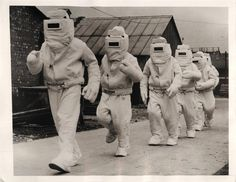 1940- Members of a British Fleet Air Arm rescue squad shown in asbestos suits designed for fire fighting.
