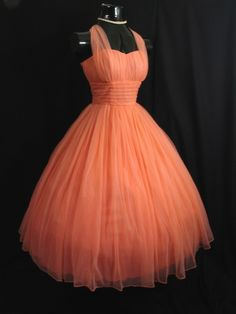 An absolutely stunning 1950's party/prom dress in a gorgeous shade of peach chiffon! The style typifies the 50's - oh so feminine and figure flattering – narrow draped bodice, designed to enhance the bust
